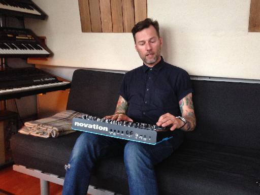 Liam Howe shows off his Novation Bass Station upon a comfy couch!